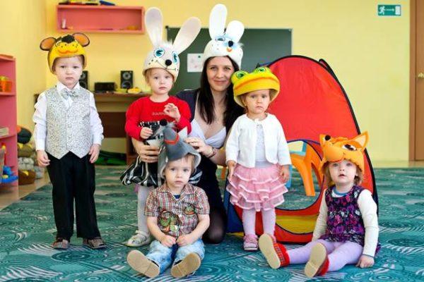 Воспитательница в шапочке с ушками зайца и дети в шапочках зайца, мышки, лисы, лягушки и медведя