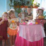 Дети играют в чаепитие за накрытым столом