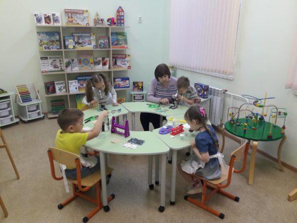 Дети, сидя за столами, работают с микроскопами, педагог помогает