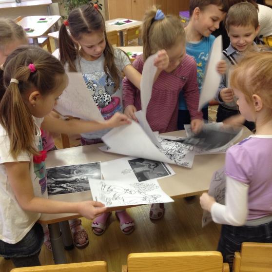 Старшие дошкольники рассматривают чёрно-белые картинки, разложенные на столе