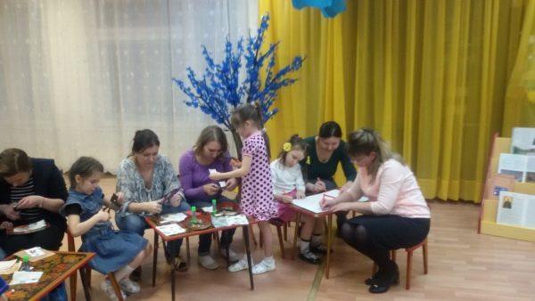 Дети и родители, сидя за столиками, мастерят поделки