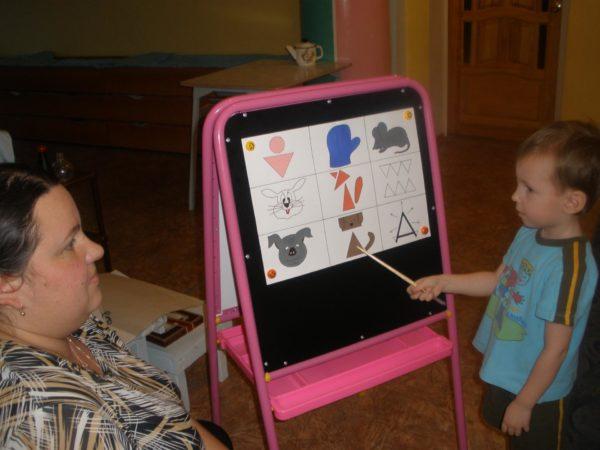 Мальчик показывает указкой на элемент мнемотаблицы, педагог внимательно слушает