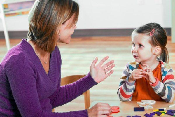 Девочка отвечает на вопросы сидящего рядом педагога