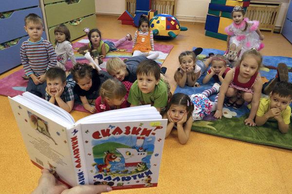 Дети лежат или сидят на ковриках и рассматривают иллюстрации в книге