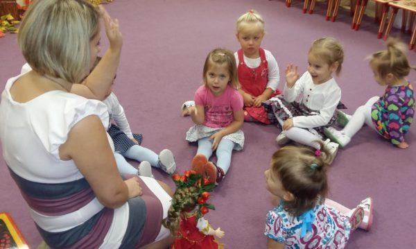 Младшие дошкольники сидят на ковре и отвечают на вопросы воспитателя