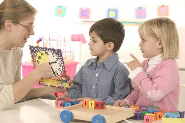 Педагог показывает мальчику и девочке настенные часы