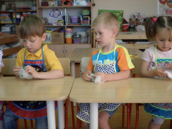 Дети сидят за столами в фартуках и держат в руках пакетики с песком