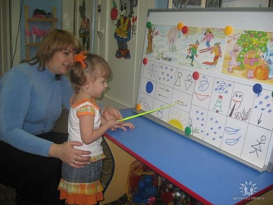 Воспитатель помогает девочке воспроизводить текст по мнемотаблице