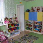 Жёлто-голубой шкаф с нишей, заполненной игрушками, три детские колясочки слева
