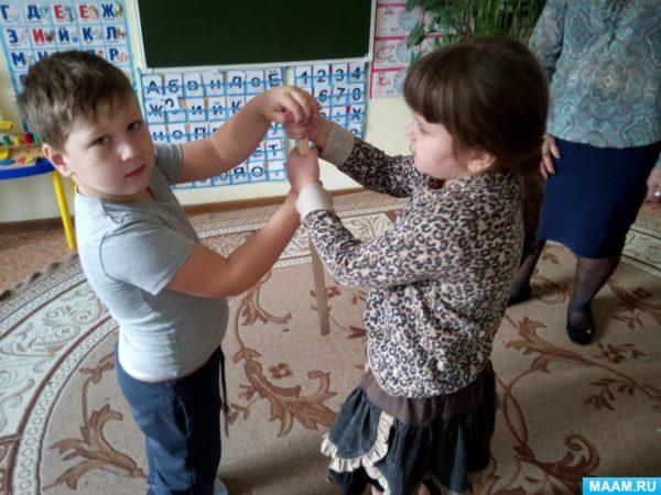 Мальчик и девочка играют с деревянной палочкой