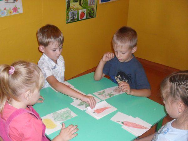 Четверо детей играют в игру «Вершки и корешки»