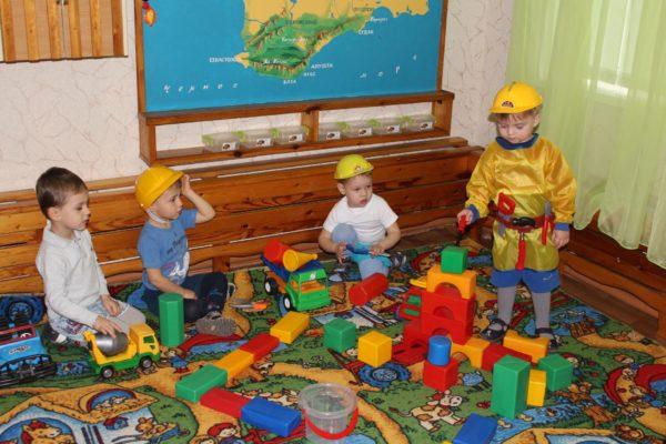 Четыре мальчика в жёлтых касках играют с машинками и строительным материалом