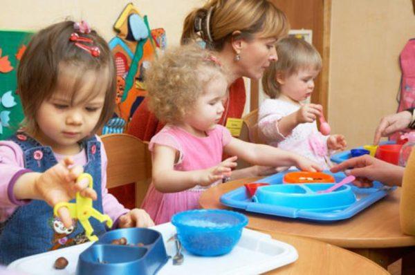Малыши перекладывают мелкие предметы с помощью пластиковых ложечек и щипцов