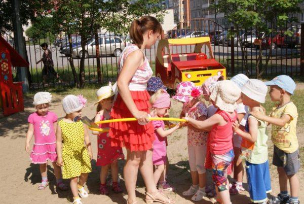 Дети держатся за обруч, в котором стоит воспитательница
