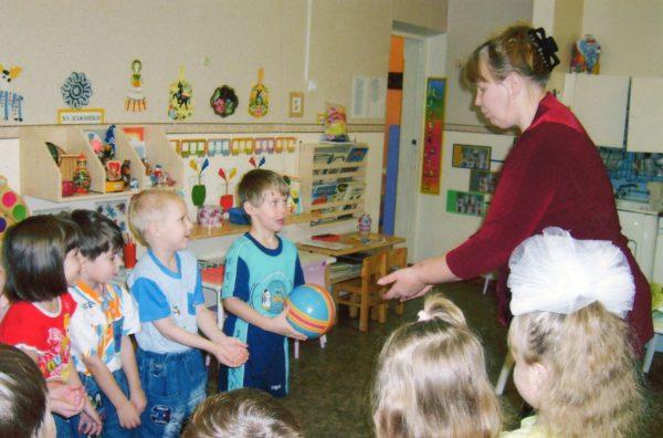 Дети и педагог играют в словесную игру с помощью мяча