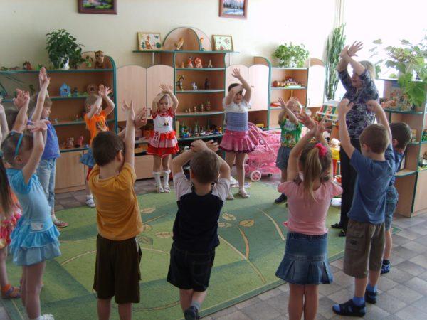 Дети и педагог стоят в кругу, подняв руки верх