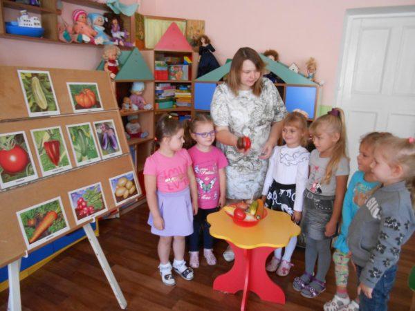 Дети и педагог стоят возле стенда с картинками с изображениями овощей