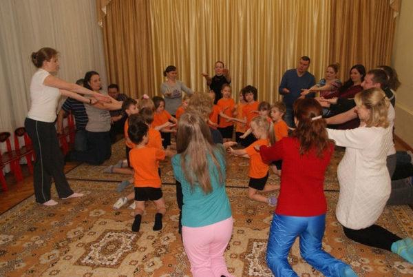 Дети и родители выполняют спортивное упражнение, стоя на коленях