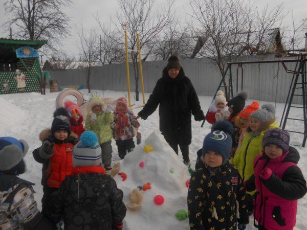 Дети и воспитательница стоят вокруг кучи снега