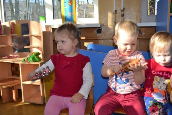Трое детей издают звуки погремушками
