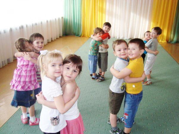 Дети обнимаются по парам в танцевальном зале