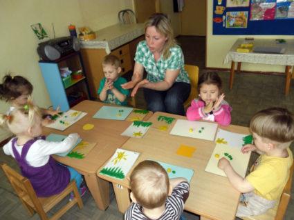Дети из пластилина делают подсолнухи на листах бумаге