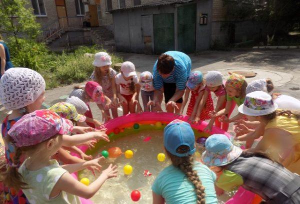 Дети ловят руками шарики в надувном бассейне