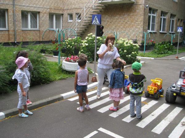 Дети на макете пешеходного перехода на территории ДОУ