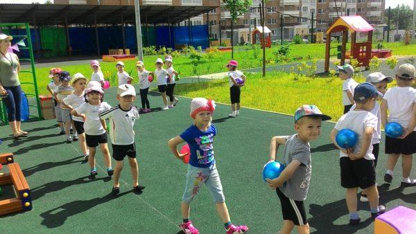 Дети на площадке выполняют упражнение с мячами