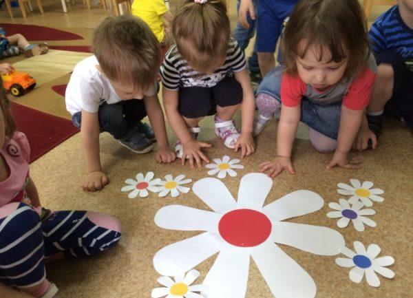 Дети сидят на ковре вокруг бумажных ромашек