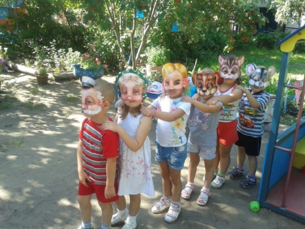 Дети на прогулке стоят в шапочках паровозиком
