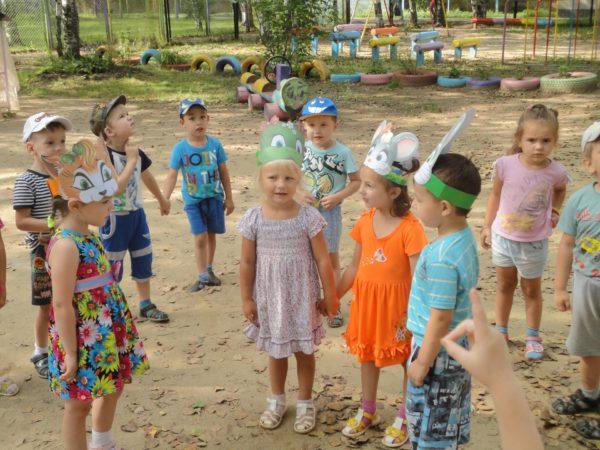 Дети на улице в шапочках-масках лягушки, зайцев и лисы