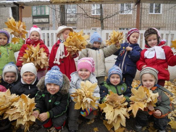 Дети на улике с букетиками осенних листьев в руках