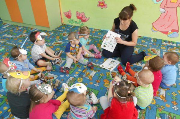 Дети с масками птиц на головах сидят на ковре и слушают педагога