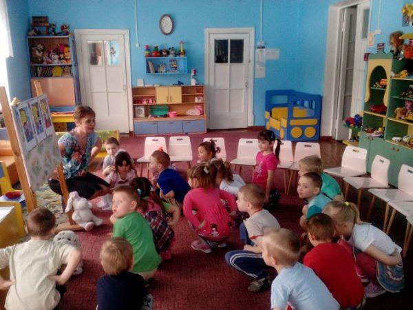 Дети и педагог присели в помещении группы