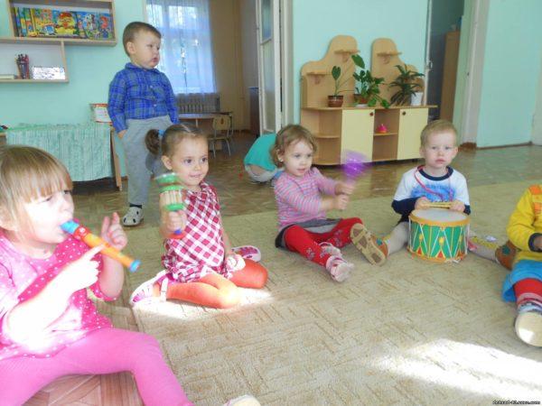Дети, сидя на ковре, играют на различных музыкальных инструментах