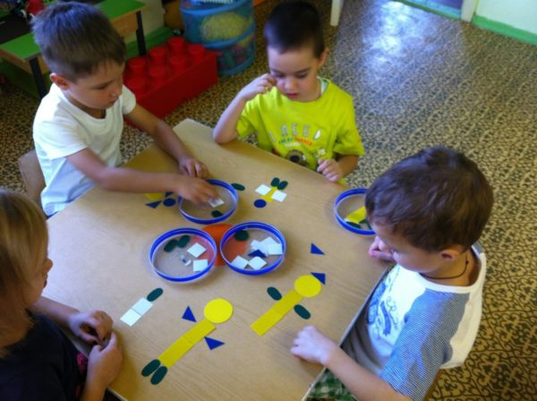 Дети, сидя за столом, составляют человечков из геометрических фигур