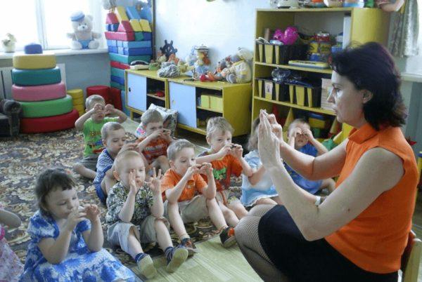 Дети сидят на коврике и вместе с воспитательницей делают пальчиковые упражнения