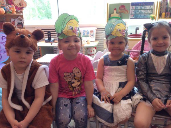Дети сидят в костюмах и шапочках-масках сказочных героев
