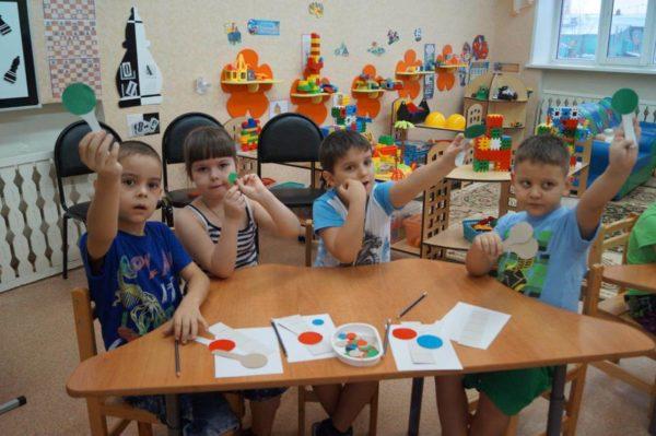 Дети сидят за столом и поднимают вверх зелёные кружочки