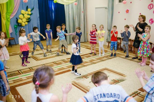 Дети и педагог стоят по кругу в танцевальном зале, одна девочка стоит в центре