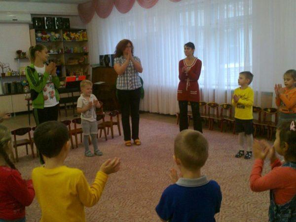 Дети стоят в кругу и повторяют движения взрослых