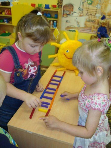 Две девочки строят лесенку из палочек к солнышку