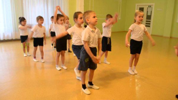 Дети в белых футболках и чёрных шортах на зарядке