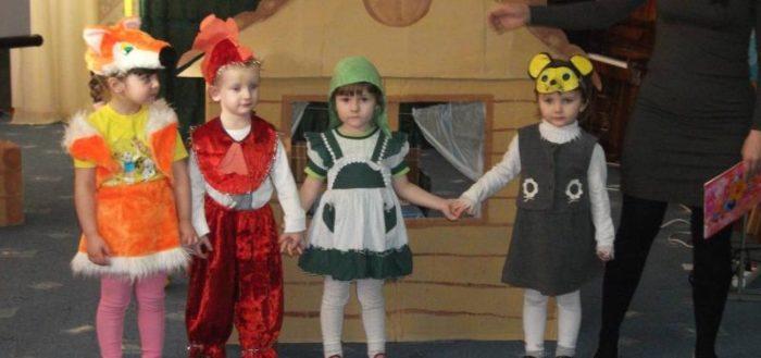 Дети в костюмах и педагог стоят на сцене