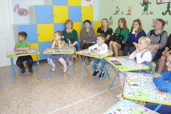 Дети выполняют задание за столиками, взрослые наблюдают
