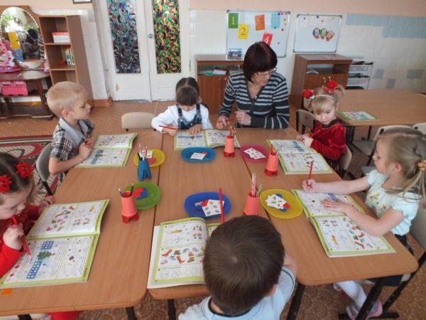 Дети выполняют задания в специальных тетрадках, педагог объясняет