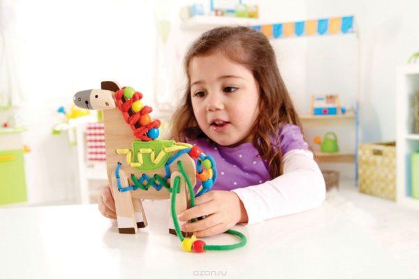 Девочка играет со шнуровкой
