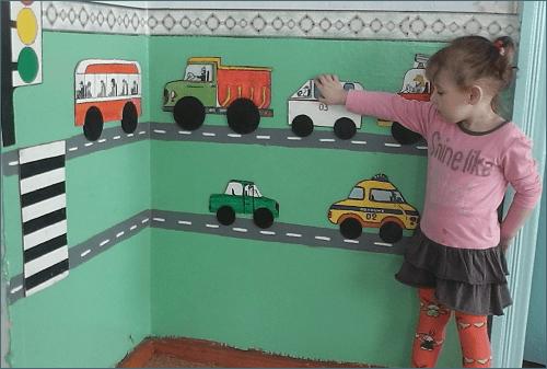 Девочка передвигает машинки на стене с макетом дороги