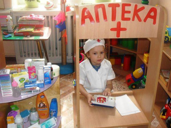 Девочка в декорациях аптеки
